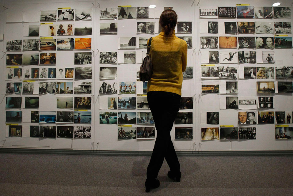 A-visitor-looks-at-a-wall-of-pictures-during-a-media-preview-ceremony-before-the-opening-of-the-exhibition-of-U.S.-photographer-Annie-Leibovitz-in-Moscow